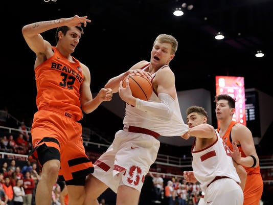 Stanford forward Michael Humphrey, center, grabs a rebound next to Oregon State forward Seth Berger (32) during the first half of an NCAA college basketball game Thursday, Feb. 1, 2018, in Stanford, Calif. (AP Photo/Marcio Jose Sanchez)