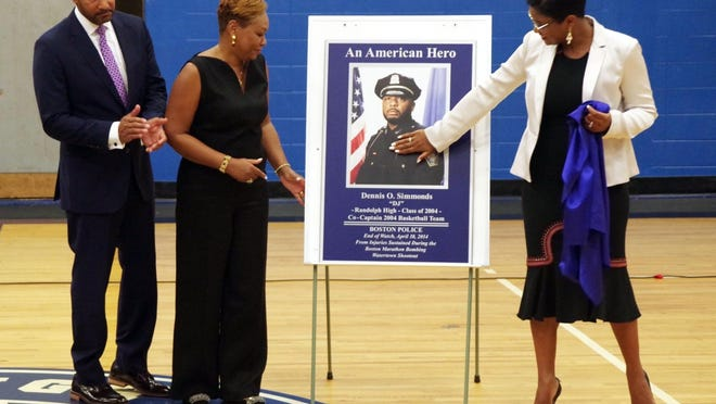 The Randolph High School gym was named in memory of DJ Simmonds in 2017. During that dedication ceremony, Nicole Simmonds, sister of DJ, gives a loving caress to the plaque she unveiled as her parents, Dennis and Roxanne Simmonds, look on.