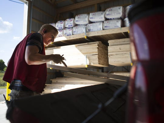 Mike Leubner loads 2-by-4s into a customer's truck in the new lumber yard at Crocker's Ace Hardware Store in Le Roy on Friday.