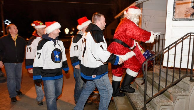Members of the Fraternal Order of Police make a surprise visit Wednesday, Dec. 23 with gifts to a family in St. Joseph.