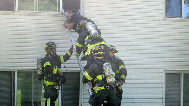 A resident of the Sundial Apartment building clutches the ladder as firefighters help him out of his second-story window to safety on Monday, Aug. 22, in Waite Park.