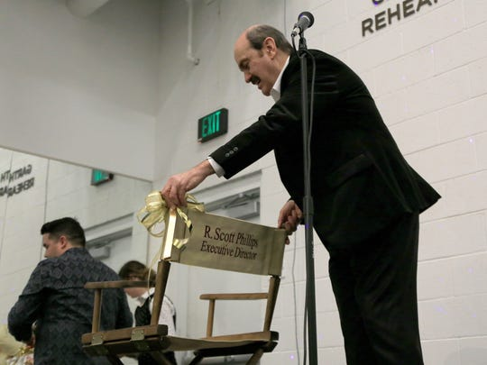 R. Scott Phillips, the former executive director of the Utah Shakespeare Festival, accepts a gold director's chair from the festival staff during a Feb. 27 retirement celebration in Cedar City.