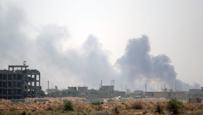 Smoke rises from buildings in Fallujah as members of the Iraqi government forces clear the streets of roadside bombs and booby traps on June 23, 2016.