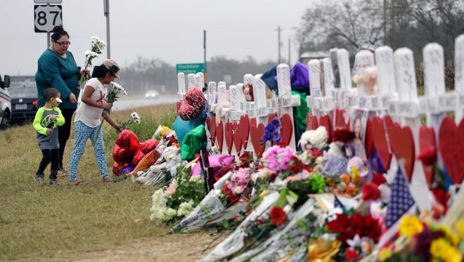 Christina Osborn and her children Alexander Osborn and Bella Araiza visit a makeshift memorial for the victims of the shooting at Sutherland Springs Baptist Church, Sunday, Nov. 12, 2017, in Sutherland Springs, Texas.