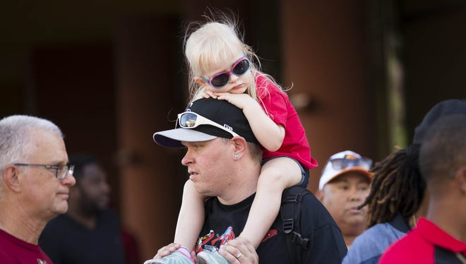 Jeremy Sawyer, from Denver, carries his daughter Teagon, 3, on his shoulders during the Opening Day Street Festival outside Chase field before the Arizona Diamondbacks open the season against the Colorado Rockies in Phoenix on April 4, 2016.