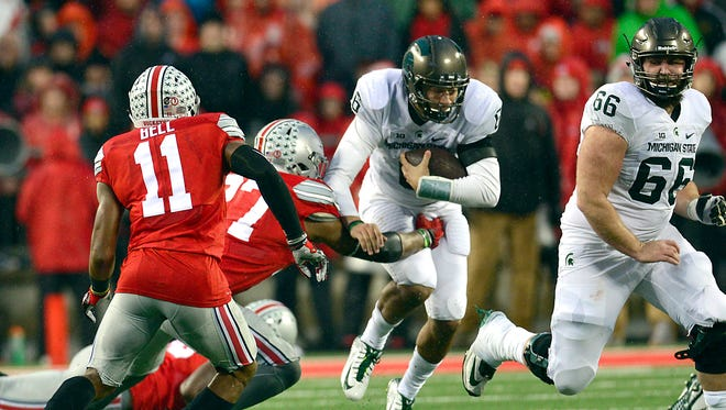 Ohio State's Joshua Perry (77) reaches for Michigan State quarterback Damion Terry as he runs through a gap in the line in the second quarter.
