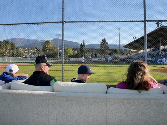 Port Angeles Lefties fans sit on couches on the third base side on a clear day with the Olympic Mountains in the background at Civic Field in Port Angeles.