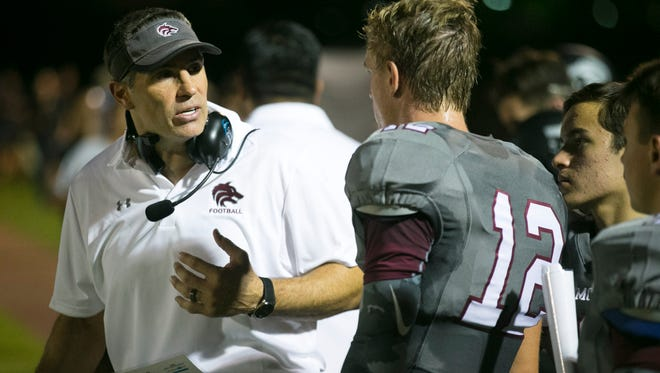 Scottsdale Desert Mountain High offensive coordinator Kurt Warner talks with quarterback Austin Nuessle during the first half of a game against Queen Creek High at Desert Mountain High in Scottsdale on Friday, Aug. 21, 2015.