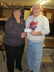 Auxiliary President Karen Delis presents a check for $604 to Jim Campbell, co-chairman of the Never Forgotten Honor Flight.