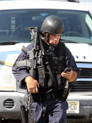 An Ocean County Regional SWAT team member walks through the parking lot of New Egypt High School near the Evergreeen Road home where a man killed his wife in New Egypt Tuesday, August 25, 2015.  That man was taken into custody and transported to Jersey Shore University Medical Center.