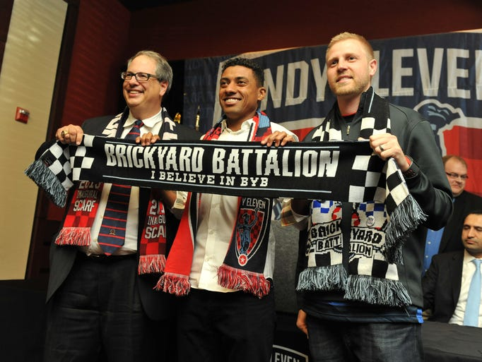 Indy Eleven President Peter Wilt, left, Brazilian midfielder Kleberson, and Gabe Peters from the Indy Eleven fan club Brickyard Battalion, pose with a Brickyard Battalion scarf after it was announced that Kleberson has signed with the Indy Eleven professional soccer club, Monday March 31, 2014. A member of the 2002 World Cup Championship team from Brazil, and a former player with Manchester United in the Premier League, joins the Indy Eleven team on a two-year contract.