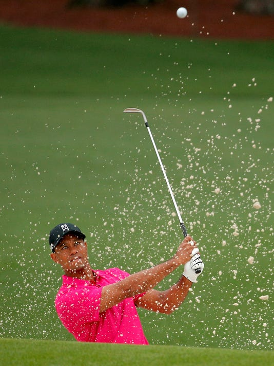 Tiger Woods hits from a sand trap to the second green during his practice round ahead of the 2015 Masters at the Augusta National Golf Course in Augusta