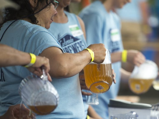 Volunteers pour beer during the 2016 Colorado Brewers'