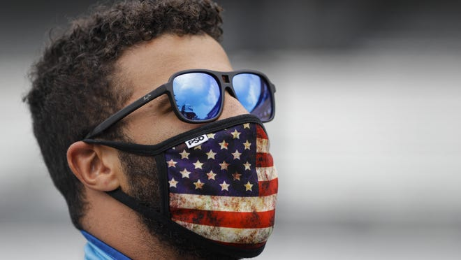 NASCAR driver Bubba Wallace checks the sky during a weather delay before the start  of the NASCAR Cup Series race at Indianapolis Motor Speedway in Indianapolis, Sunday, July 5, 2020.