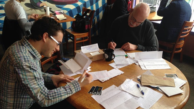 Volunteers Bill Boulden, left, and Jim Oliver write letters to prisoners at the first meeting of the Freethought Books Project Correspondence Club in Buffalo.