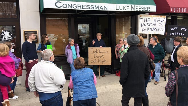 Charlie Winslow addresses a group of demonstrators Tuesday in front of Rep. Luke Messer's office in Muncie.