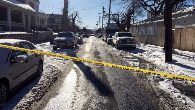 Crime tape stretches across a road near the scene of a shooting Thursday, Jan. 18, 2018, in Harrisburg, Pa. The mayor of Harrisburg said a U.S. marshal is dead after being shot while serving an arrest warrant in the city. Mayor Eric Papenfuse said two other officers were wounded in the Thursday morning shooting.