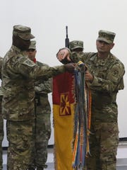 "Col. Issac ""Ike"" Gipson, left, and Command Sgt. Maj. Paul Albright uncase the brigade colors during the transfer of authority ceremony in the Middle East."