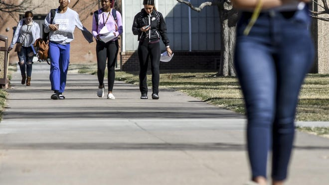 A group of students make their way between classes in March on the campus of Garden City Community College, the week before classes were moved to online only.