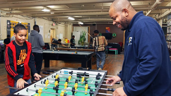 Keelyn Tyler II, 10, (left) plays foosball with his father Keelyn Tyler, a mentor at the Running Rebels.The Rebels are expanding their mentorship program thanks to a grant from Potowatomi.