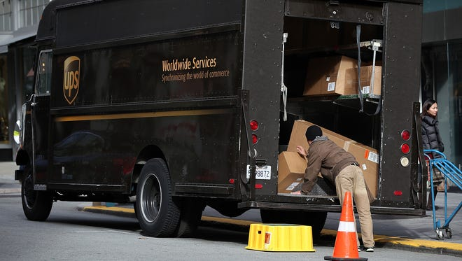 A UPS driver unloads packages in this December 2012 file photo.