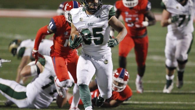 CSU running back Izzy Matthews breaks through the Fresno State defense on a 19-yard touchdown run Saturday night. The Rams beat the Bulldogs 34-31 to finish the regular season with a 7-5 record.