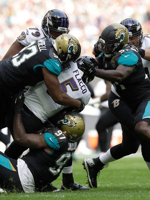 Baltimore Ravens quarterback Joe Flacco (5) is sacked by the Jacksonville Jaguars defense during an NFL football game at Wembley Stadium in London, Sunday Sept. 24, 2017. (AP Photo/Matt Dunham)