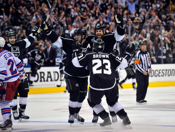 Los Angeles, CA, USA; Los Angeles Kings right wing Dustin Brown (23) celebrates with defenseman Willie Mitchell (right) and center Anze Kopitar (11) after scoring the game-winning goal in the second overtime period.