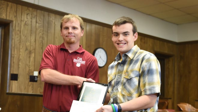 Jathan Fox was presented with the Leone M. Bailey 4-H Achievement Award and $250 by Brian See, interim staff chair of the Marion County Cooperative Extension Service, during Tuesday night's Marion County Quorum Court meeting in Yellville. Award winners were selected based on their applications and their 4-h record books.