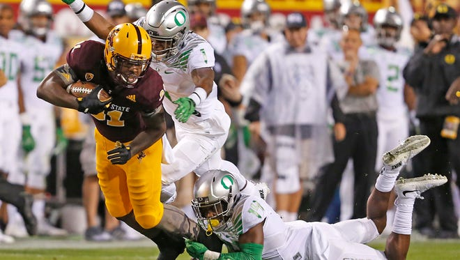Oregon's Ugo Amadi (14) and Arrion Springs (1) make a tackle on ASU's Gary Chambers (81) at Sun Devil Stadium in Tempe on October 29, 2015.