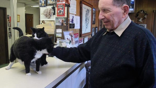 Veterinarian Herman Berg pets the two hospital cats, Mimi and Cookie, in the waiting room area of Berg Animal Hospital on Route 34 in Old Bridge, just across the boundary from Matawan.