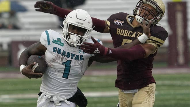 Coastal Carolina's CJ Marable runs past Texas State's Kevin Anderson during the first half in San Marcos on Saturday. The Chanticleers ran the ball well against the Bobcats in the 49-14 win.