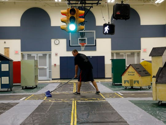 Lancaster Police Officer Chuck Sims tries to sweep out creases in the Safety Town mat Friday, June 8, 2018, at Mount Pleasant Elementary School in Lancaster. LPD officers, Lancaster City Schools employees and Lancaster Transportation Department workers were preparing for the annual safety class which begins next week.