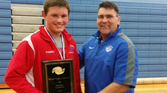 Madison's Payton Roberts is presented with his Western Highlands Conference tournament Most Outstanding Wrestler plaque from Polk County athletic director Jeff Wilson.
