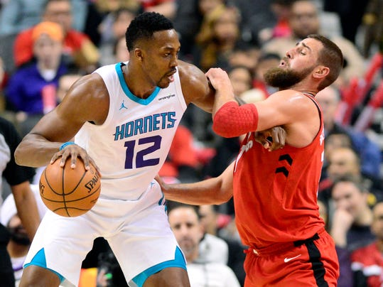 Toronto Raptors center Jonas Valanciunas is fouled by Charlotte Hornets center Dwight Howard (12) during the first half of an NBA basketball game, Sunday, March 4, 2018, in Toronto. (Frank Gunn/The Canadian Press via AP)