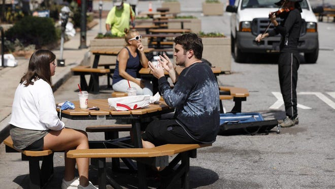 Workers have brought in 24 tables as they convert a one-block stretch of College Avenue downtown into a pedestrian mall and dining area.