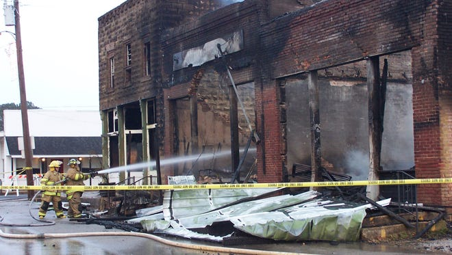 Firefighters put out hot spots in the rubble of Smith Drug Store on Main Street in Rienzi.