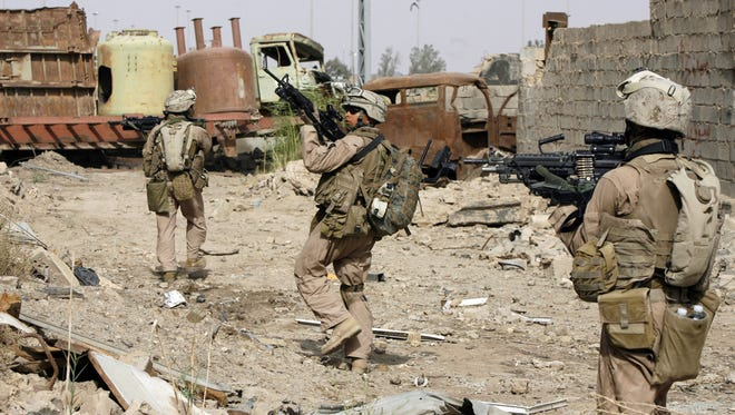 US marines aim their weapons as they walk through the rubble of an industrial building during a dismounted patrol in the southern part of Fallujah 30miles west of Baghdad 25 May 2007. US President George W. Bush will sign a key funding bill for US troops in Iraq and Afghanistan possibly as early as today, White House spokesman Scott Stanzel said.