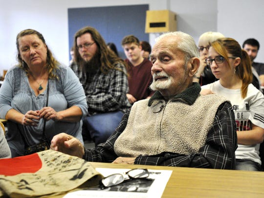 This Nov. 21, 2016 photo shows World War II veteran Marvin Strombo, right, talks to a Japanese Culture and Civilization class at the University of Montana in Missoula, Mont., about his experiences as a young Marine fighting in the Pacific during World War II. Strombo, 93, also brought a Japanese flag, on the desk in front of him, that he took from a slain Japanese officer in the Battle of Sapian that he's hoping can be returned to the man's family.