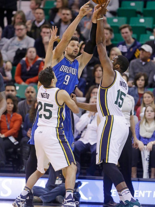 Orlando Magic center Nikola Vucevic (9) passes the ball as Utah Jazz's Raul Neto (25) and Derrick Favors (15) defend in the first quarter during an NBA basketball game Thursday, Dec. 3, 2015, in Salt Lake City. (AP Photo/Rick Bowmer)
