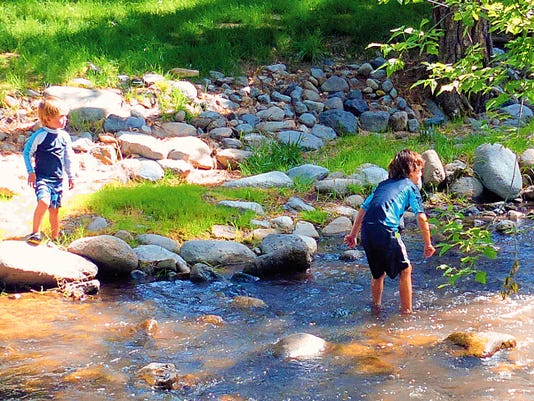 Plenty of rain is keeping the Rio Ruidoso flowing to the delight of young visitors.