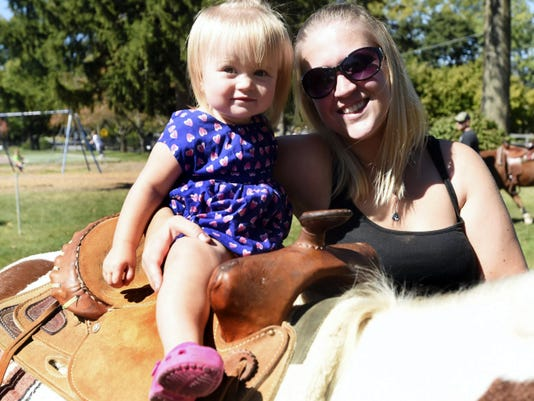 Rylinn Boyd rides a pony with the help of her mother Nikki Boyd during Mercersburg TownFest on Saturday, September 27, 2014.