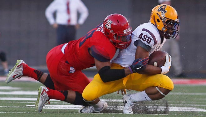 Arizona safety Anthony Lopez tackles Arizona State running back Deantre Lewis during the second half of the Territorial Cup at Arizona Stadium in Tucson on Nov. 28, 2014