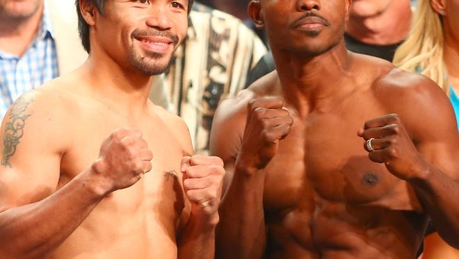 Timothy Bradley and Manny Pacquiao pose for photographs during the weigh in for their fight at the MGM Grand in Las Vegas, April 8, 2016.