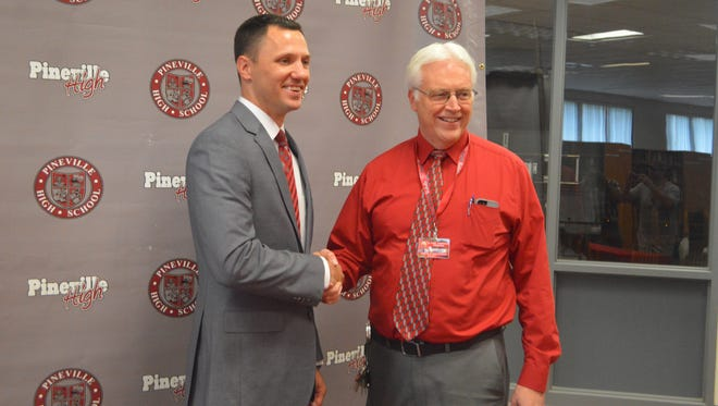 New Pineville boys basketball coach Chad Sears (left) shakes hands with principal Dr. Karl Carpenter Monday.
