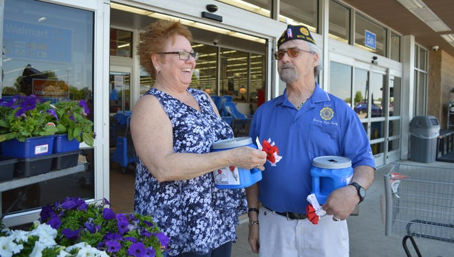Sue Adams chats with Rodney Millington while they pass out handmade poppies in front of Walmart in Bucyrus.