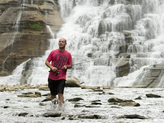 Brett MacHenry of Cortland goes to collect a friend's flip flop that got away from him while fishing at Ithaca Falls.