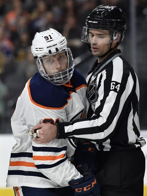 FILE - In this Feb. 15, 2018, file photo, Edmonton Oilers center Drake Caggiula is held by linesman Brandon Gawryletz during the third period of the Oilers' NHL hockey game against the Vegas Golden Knights in Las Vegas. Because NHL players are expected to be tested daily, there isn't expected to be additional on-ice equipment required for practices and games. Deputy Commissioner Bill Daly additionally said he didn't anticipate any mandatory equipment changes to ensure player safety. Still, hockey equipment manufacturer Bauer has spoken with the league and teams about medical-grade off-ice visors that coaches, executives, team personnel and others could wear as a measure of protection against spreading or contracting COVID-19.