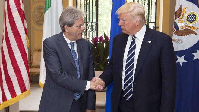 A handout picture made available by the Italian Presidency of the Council shows the Italian Prime Minister Paolo Gentiloni (L) shaking hands with President Trump (R) during their meeting at Villa Taverna in Rome on May 24, 2017.