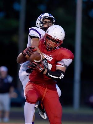 Richmond's Sean Ferguson catches a pass under coverage by Muncie Central's Noah Hill Friday, Sept. 9, 2016, during a football game on Lyboult Field. The play led to a Red Devil touchdown.